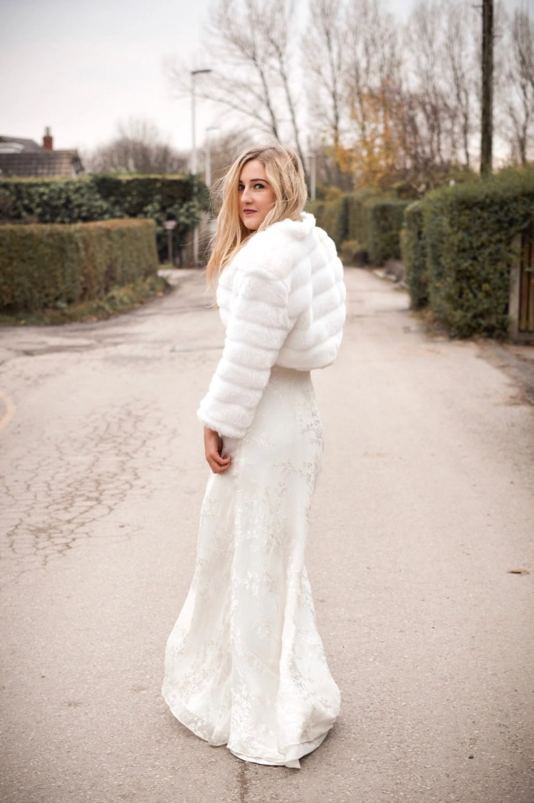 BB42 – faux fur cropped bridal jacket with sleeves on blonde bride with hair down on country lane back view