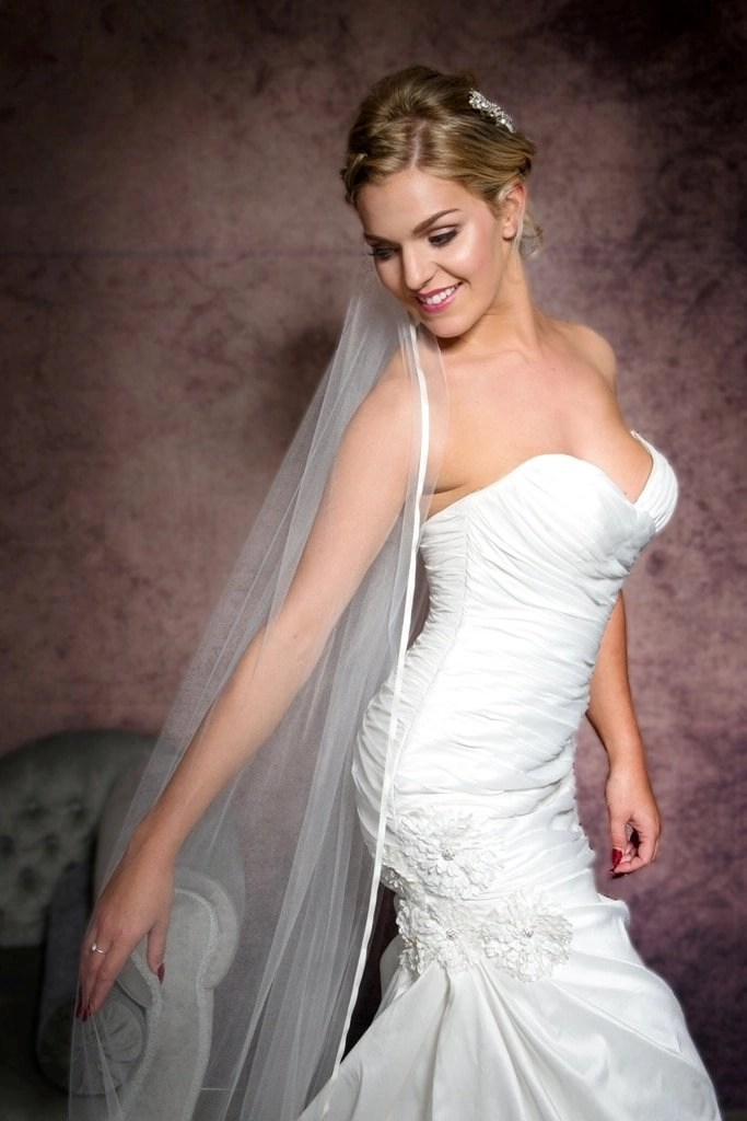 Smiling happy bride wearing a veil with ribbon edging