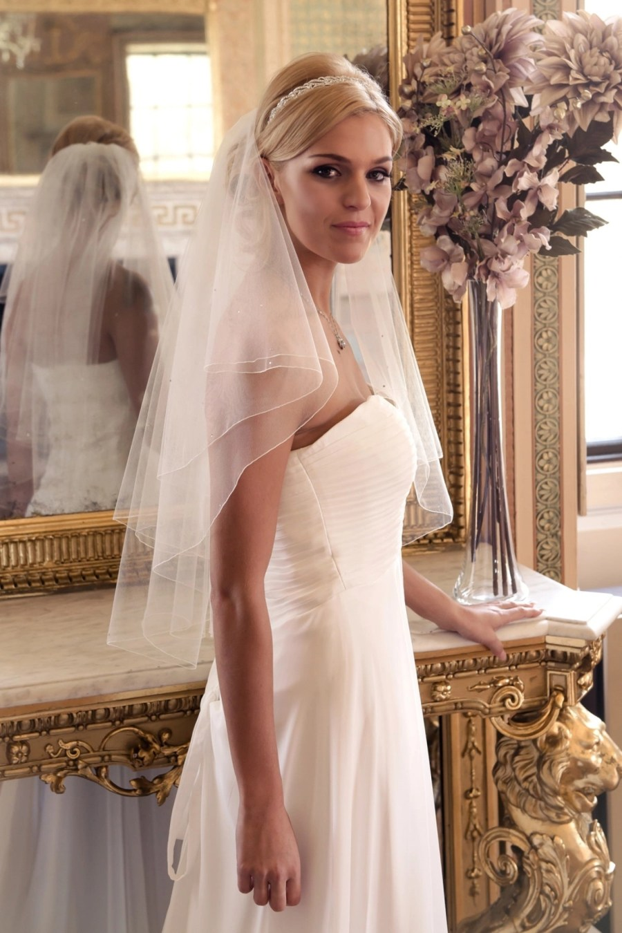 Bride in golden ballroom wearing short wedding veil with scattered diamantes