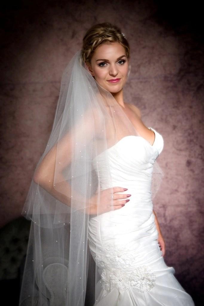 Close up of bride posing with a cut edge wedding veil