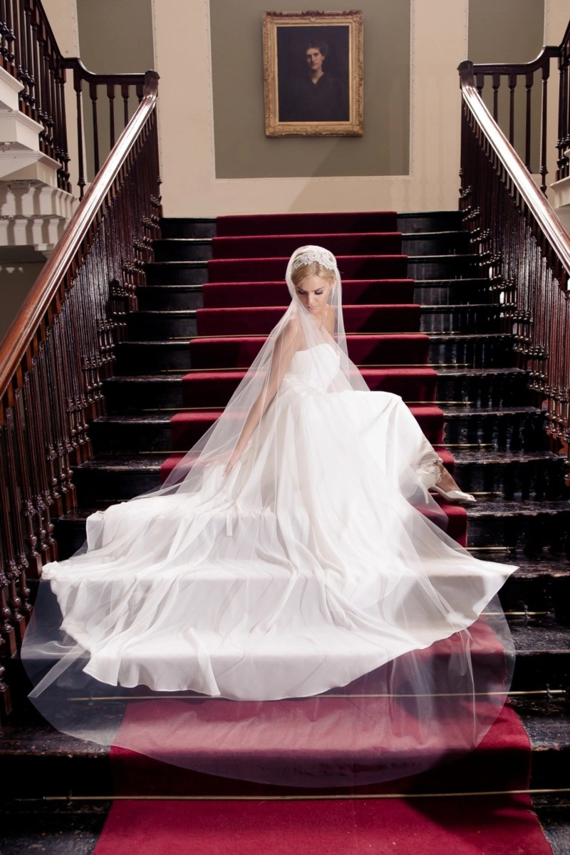 Pretty bride sat on grand staircase wearing Juliet cap veil