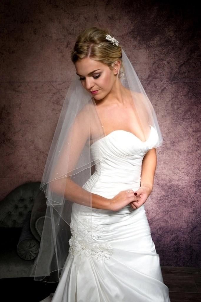 Demure bride wearing a simple fingertip length veil with diamantes
