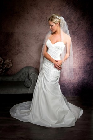 Bride posing in a single layer fingertip length veil