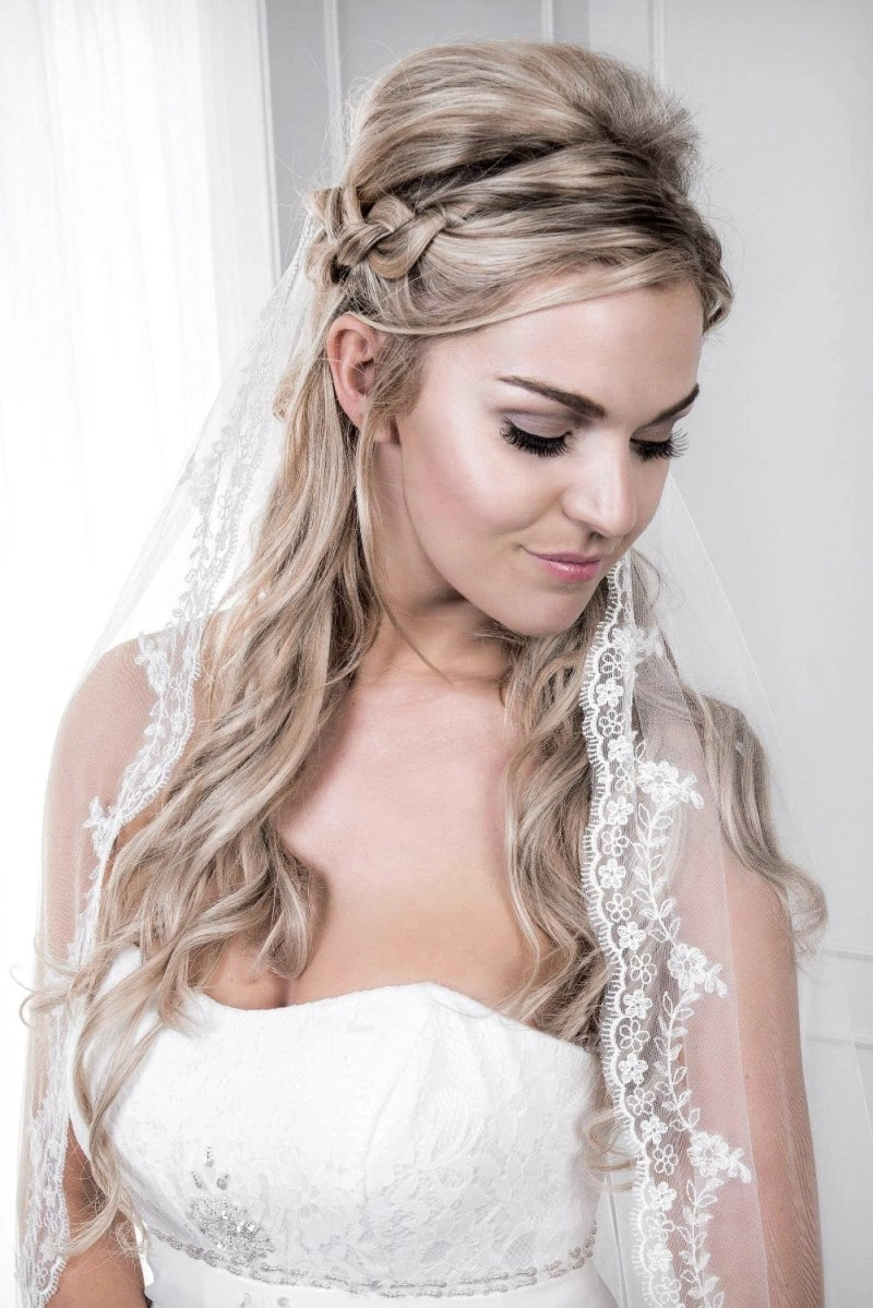 Close up of bride wearing pretty chapel length veil with eyelash lace edge