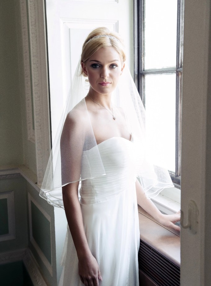 Bride at window wearing two layer elbow length single layer veil with ribbon edging