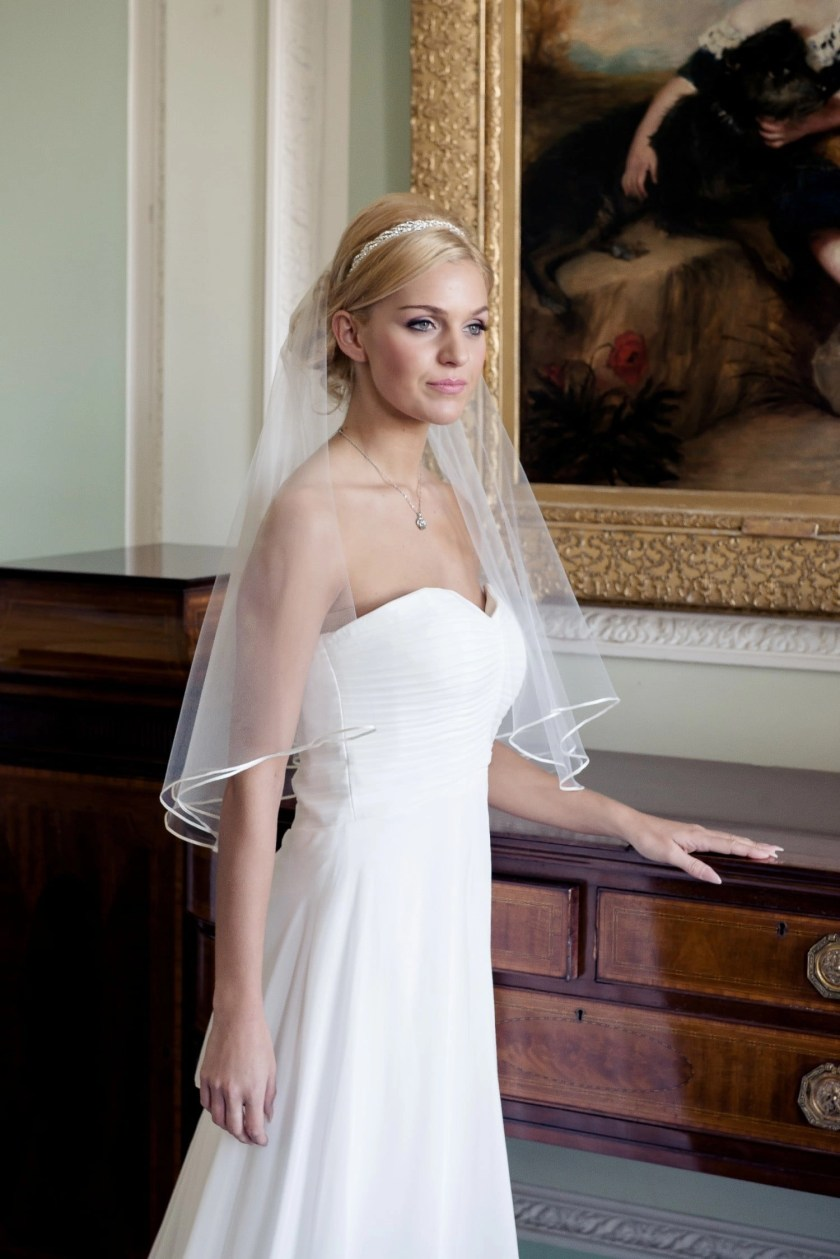 Bride wearing two layer elbow length single layer veil with ribbon edging