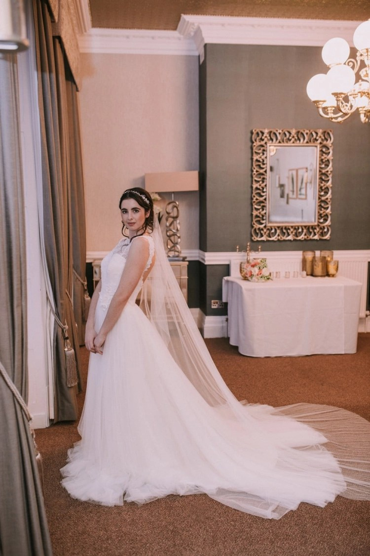 Bride wearing hand cut barely there waterfall cut chapel length veil