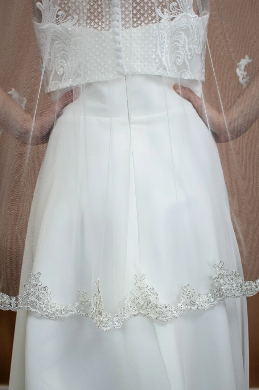 Alana - single layer hip length veil with silver and ivory lace topped with a hand beaded edge on a bride back closeup