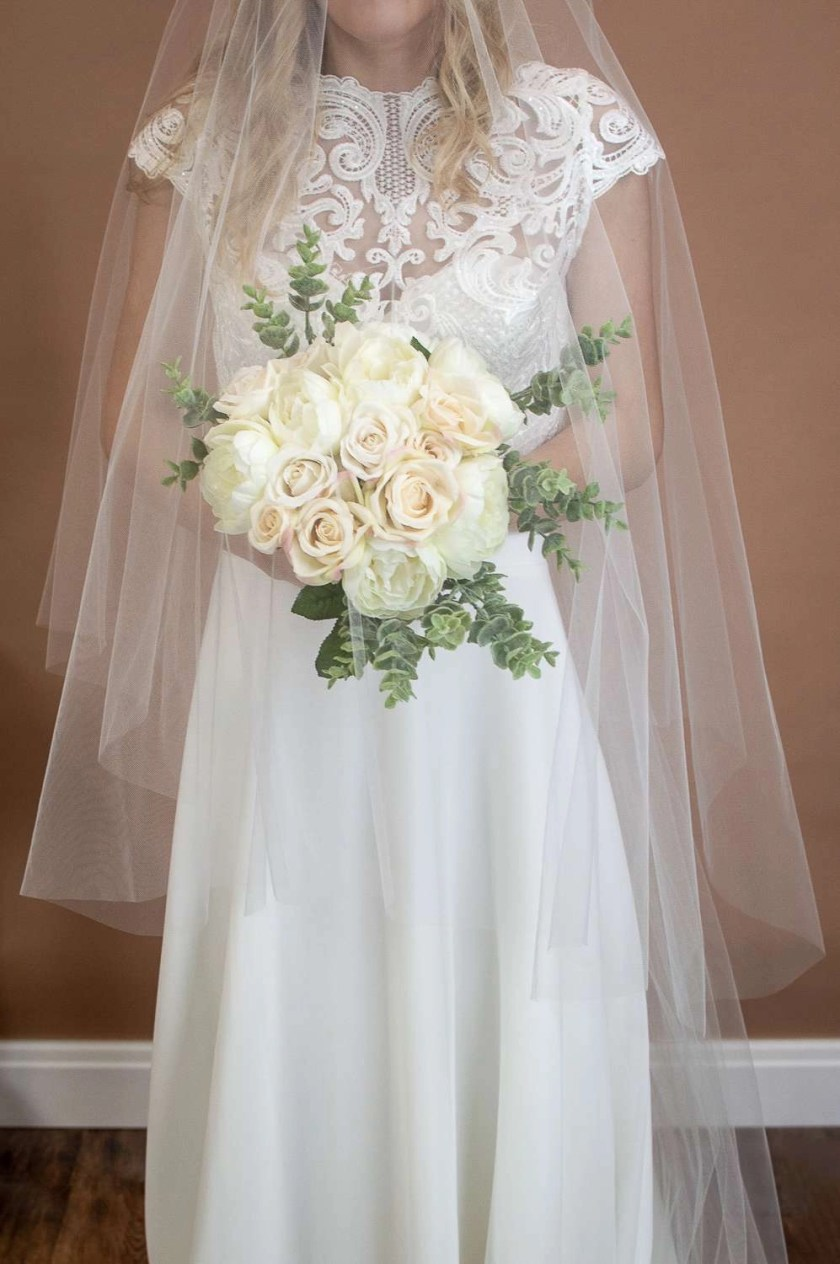 Caitlyn - two layer chapel length plain veil with a cut edge and extra long blusher on a bride closeup with flowers front view