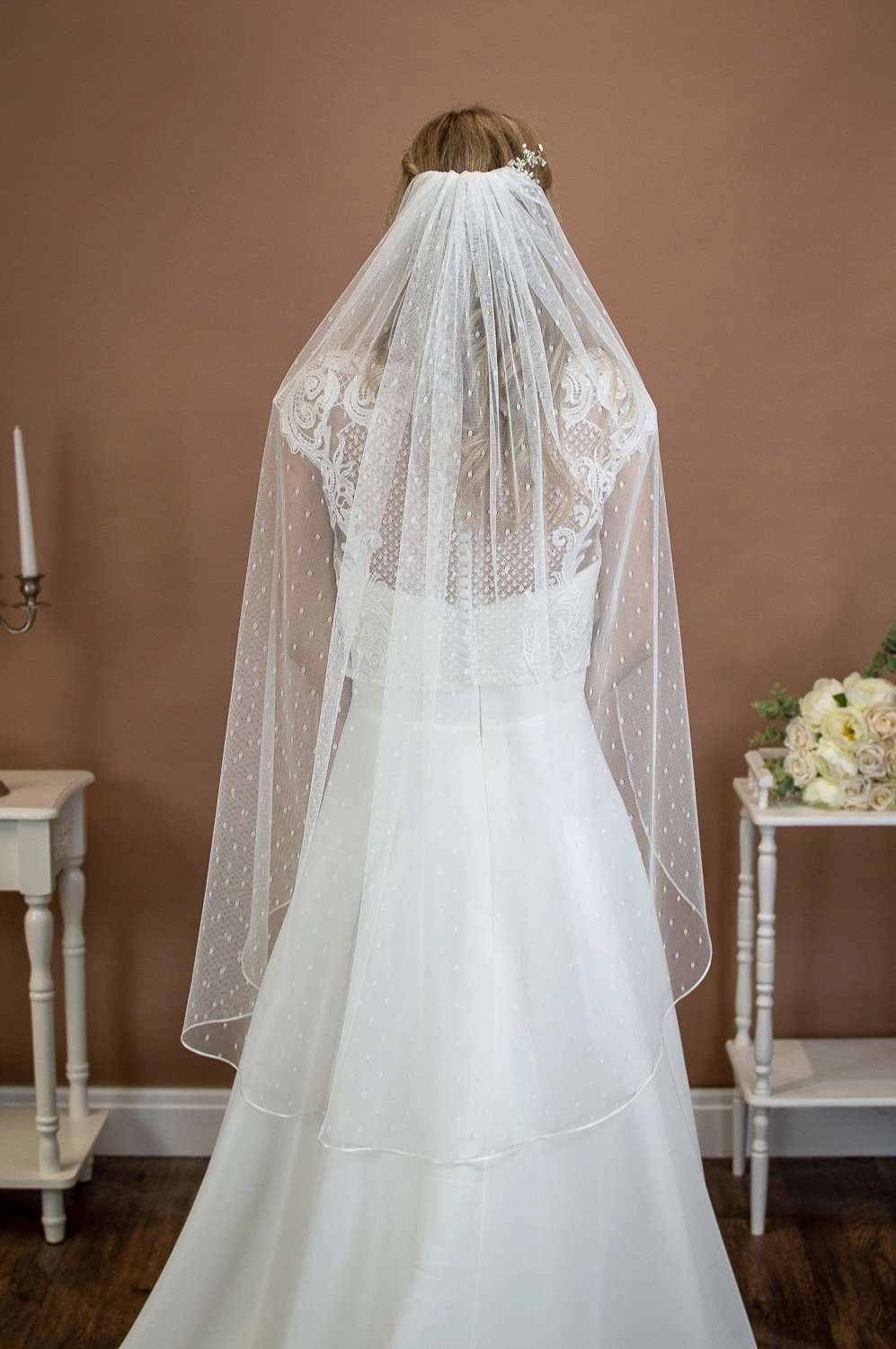 Poppy - medium fingertip length single layer ribbon edge veil in spotty dotty tulle on a bride