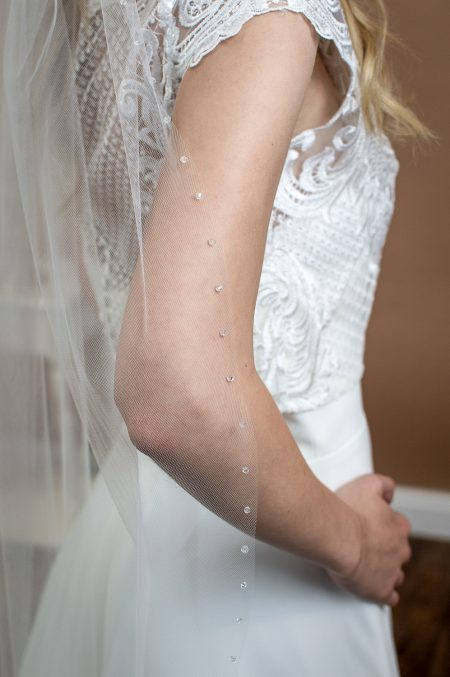 Stella - one layer fingertip length veil with a cut edge and a single row of crystals closeup