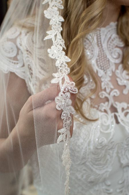 Zoe - single layer fingertip length veil with a beaded narrow floral lace closeup