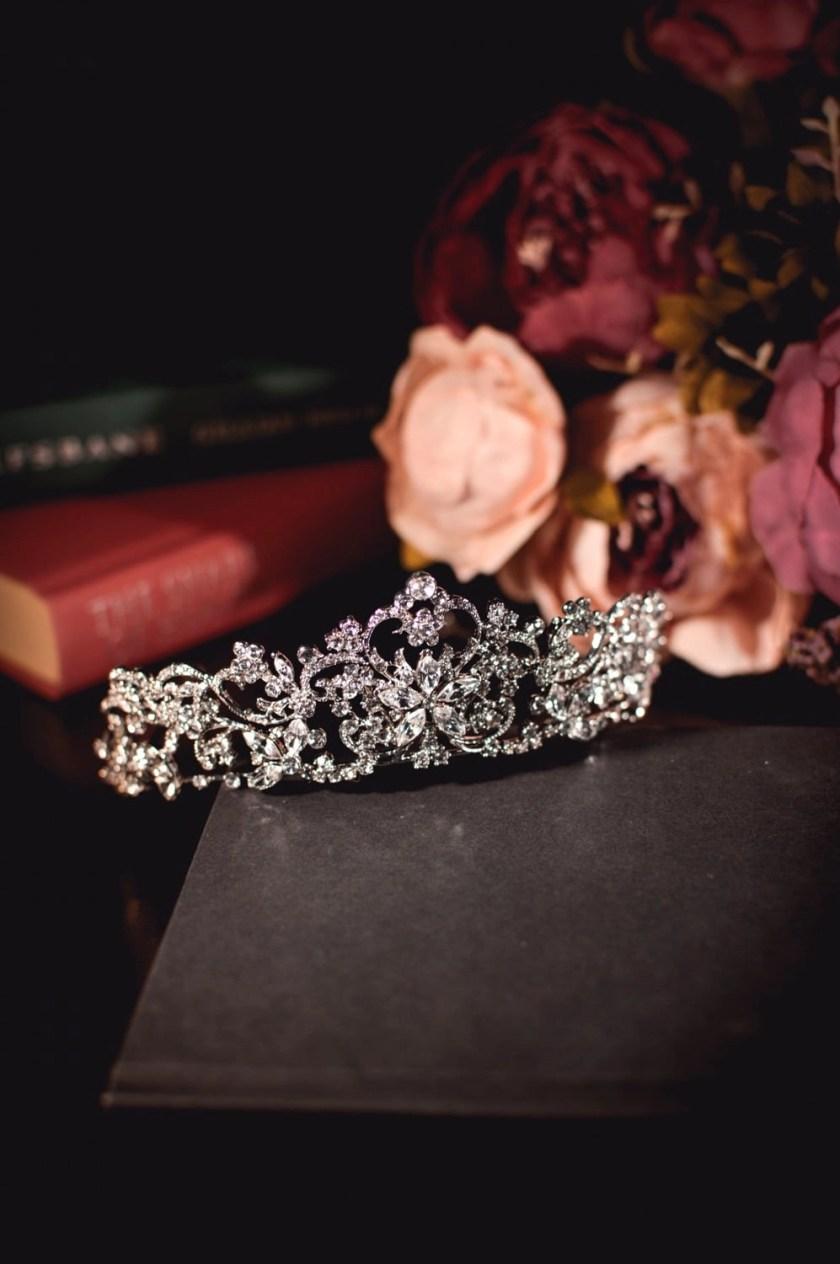 Regina large silver diamante bridal tiara closeup on books