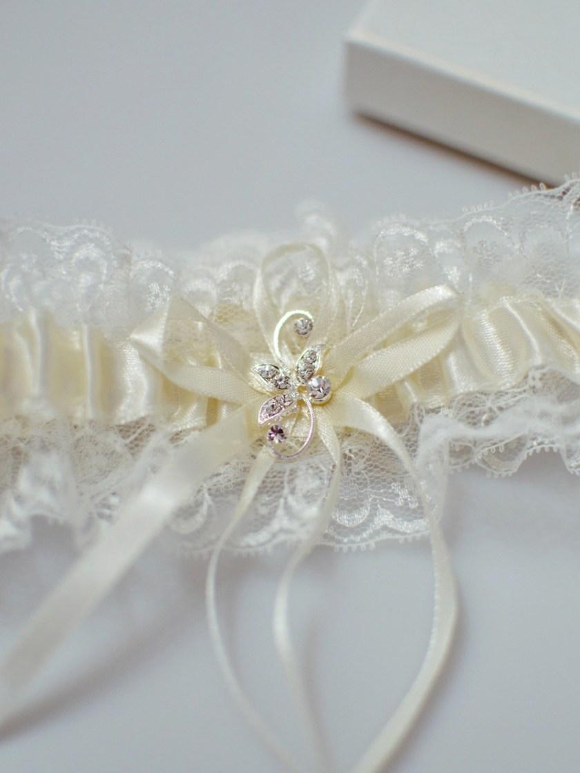 Pretty ivory wedding garter with diamante brooch detail closeup TLG511