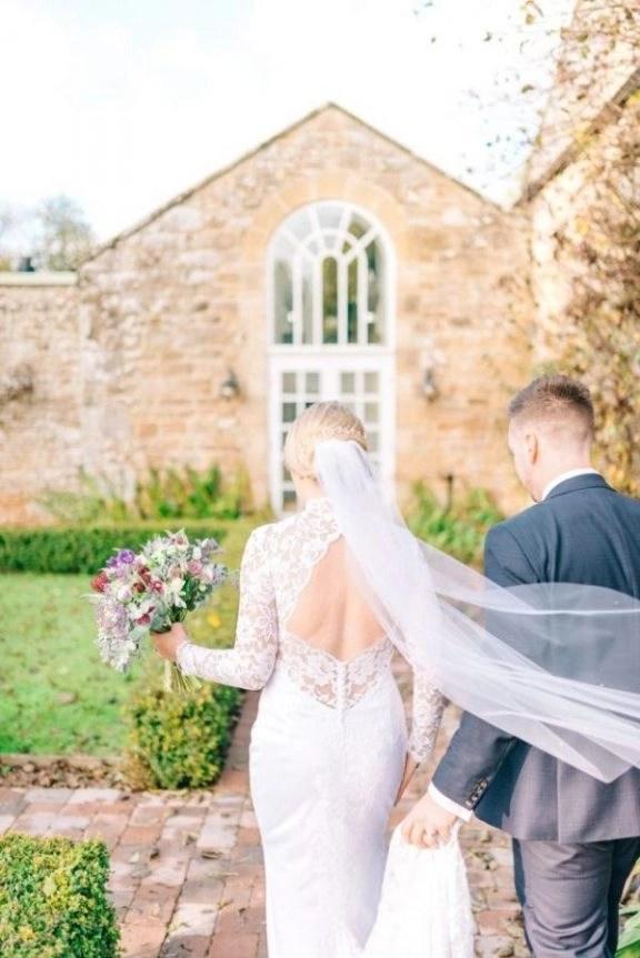 Real bride Alex wears a custom fingertip length veil with a hand cut edge