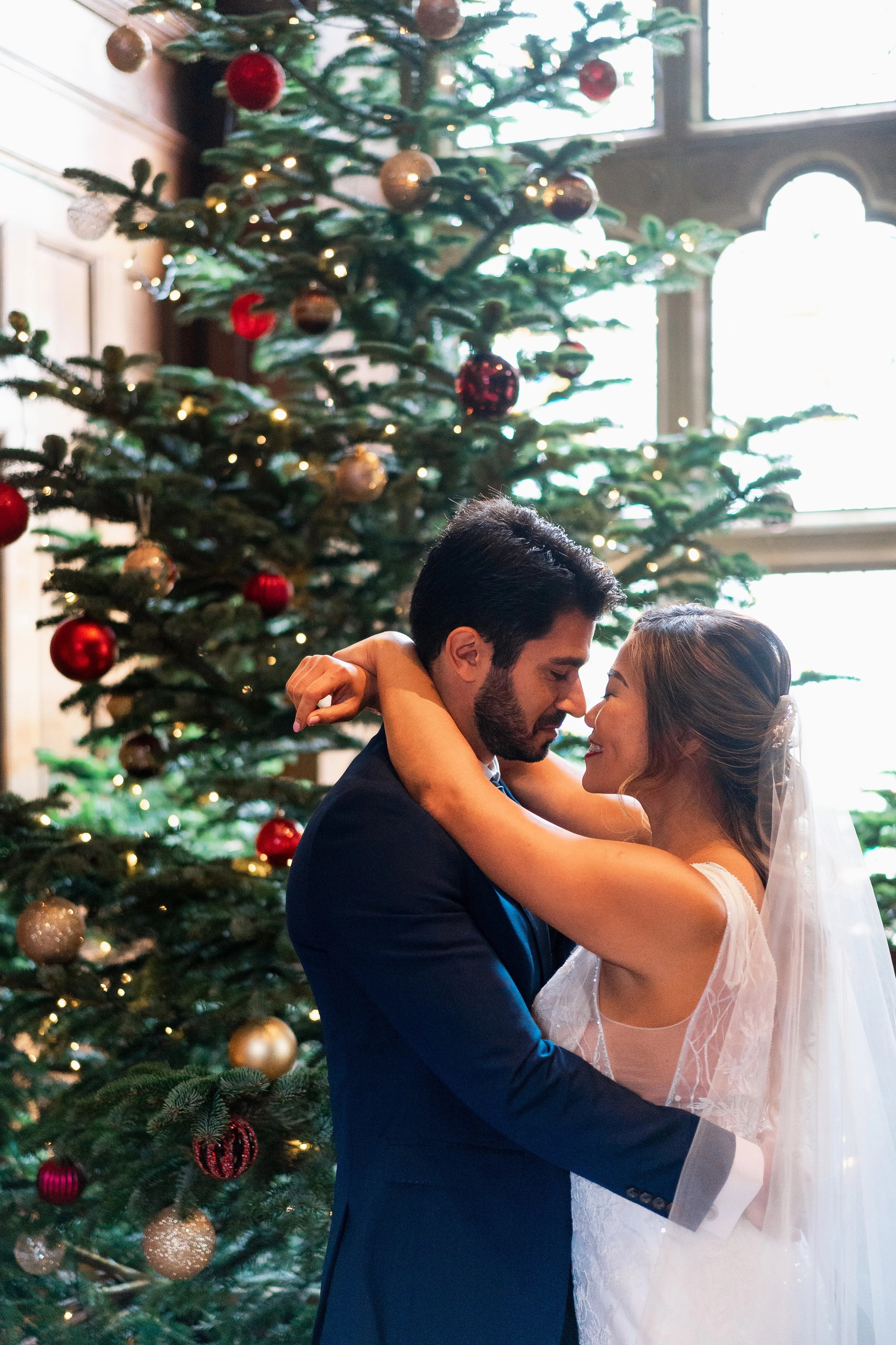 Bride and Groom close up in front of Christmas tree