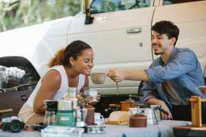 cheerful multiracial couple drinking tea during picnic in nature