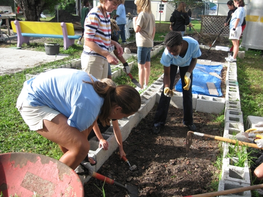 Students from Horace O'Bryant Middle School learn the basics of planting seeds in the plot they maintain