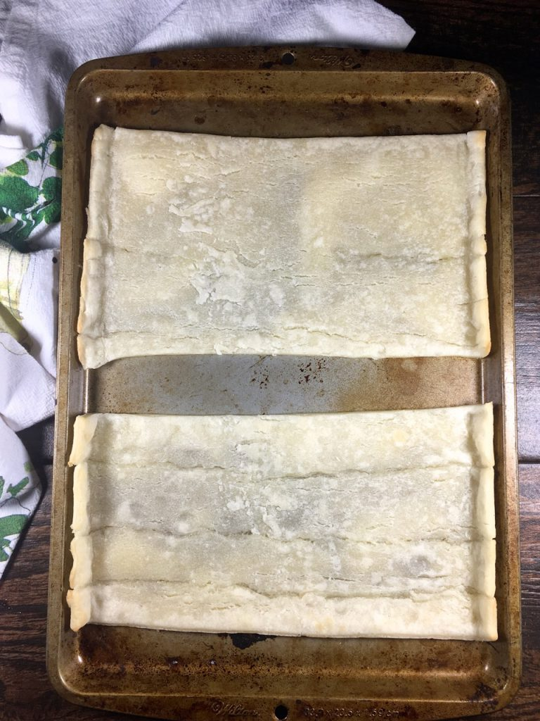 Schär gluten-free puff pastry crust cut in half on a baking sheet and cooked for 6 minutes