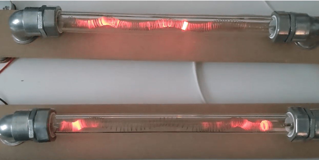 sculpture made of pyrex tube with heated metal coils glowing red inside, the ends of the tube are sealed with pipe fittings