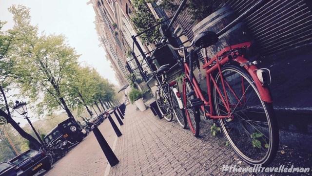 thewelltravelledman travel blog Amsterdam red bike on street