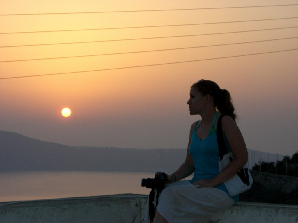 Young woman holding camera looking over city wall at the sunset over the coast