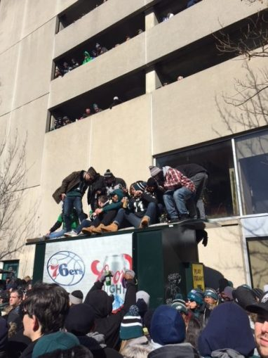 Fans perched on top of whatever they could find as the parade made its way to the steps of the art museum. -Staff Photo/Chris Devine