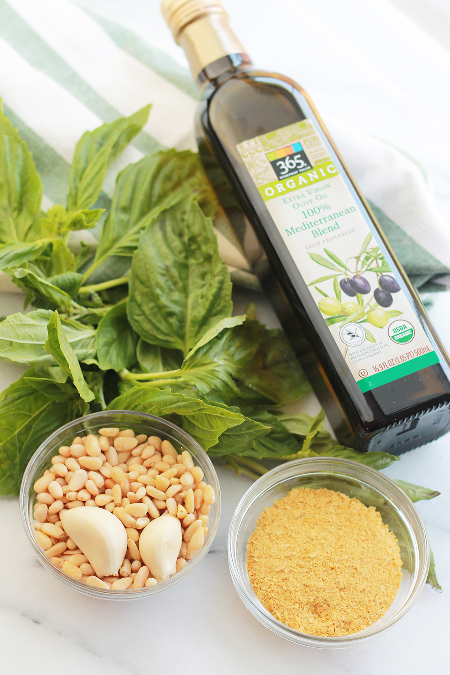 Bottle of olive oil, fresh basil, pine nuts, garlic cloves, and nutritional yeast.