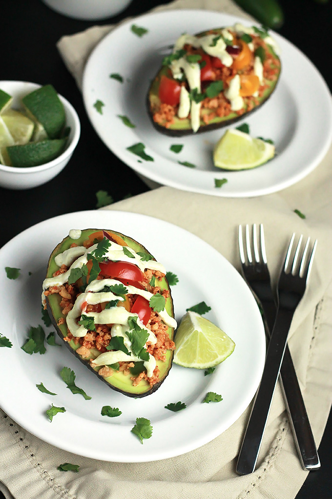 Sliced avocado stuffed with textured vegetable protein, topped with avocado cream, tomatoes and cilantro, with a wedge of lime.