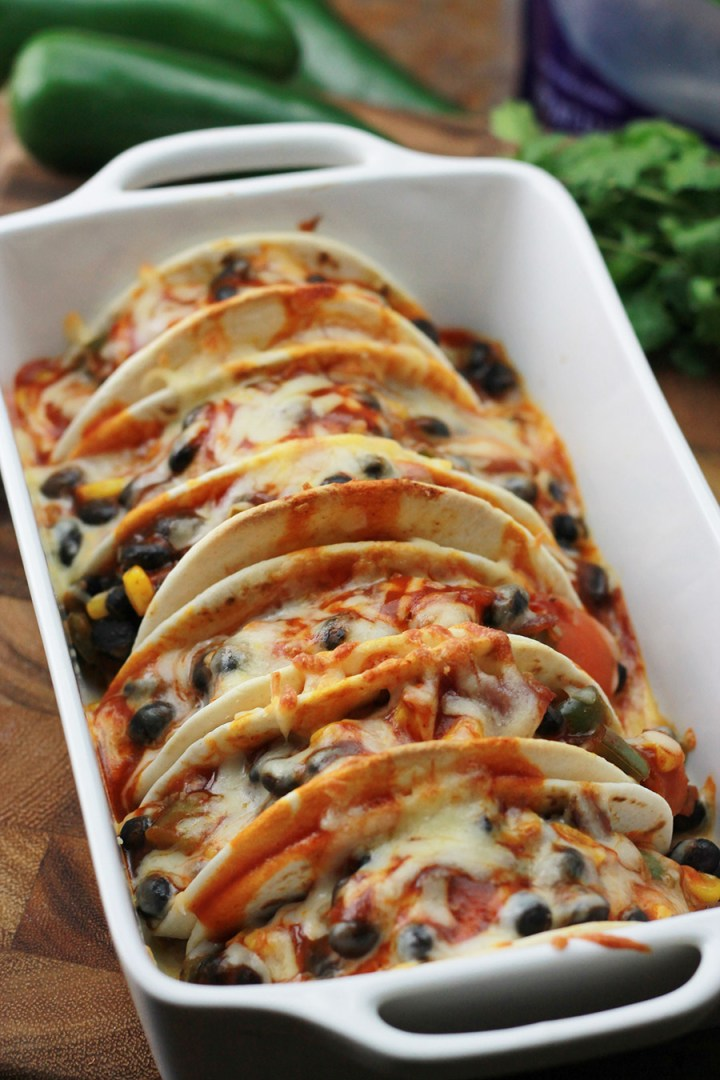 Baked Black Bean Tacos with Red Chile Sauce in baking dish.