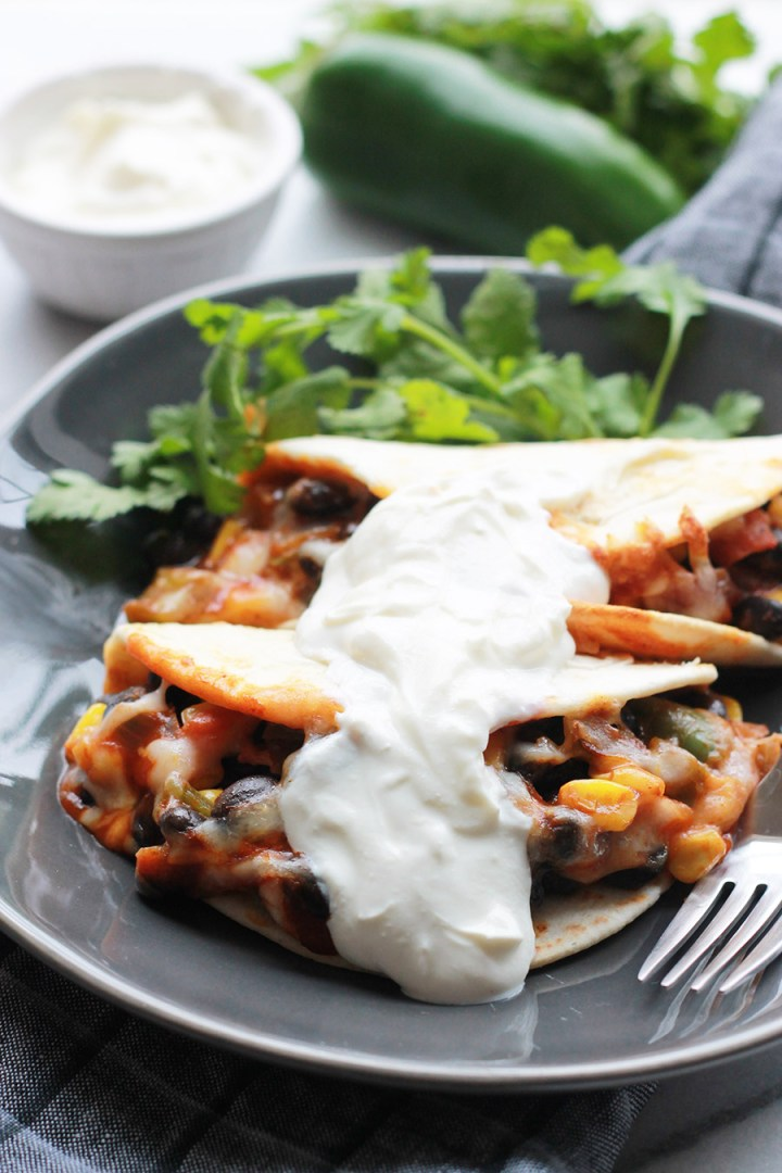 Baked Black Bean Tacos with Red Chile Sauce on plate topped with sour cream.