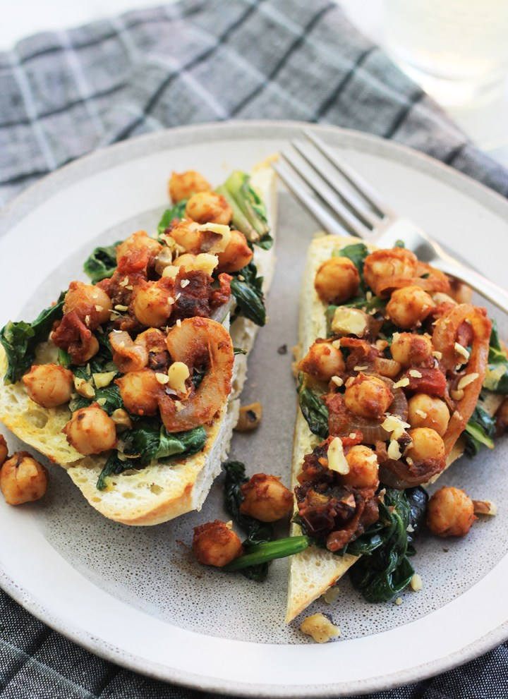 Ciabatta garlic toast with sauteed greens and chickpeas on top with a glass of wine in the background.