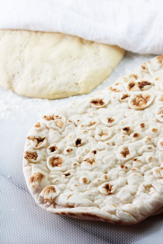 Homemade pizza dough with a white towel draped over half and nann flatbread,