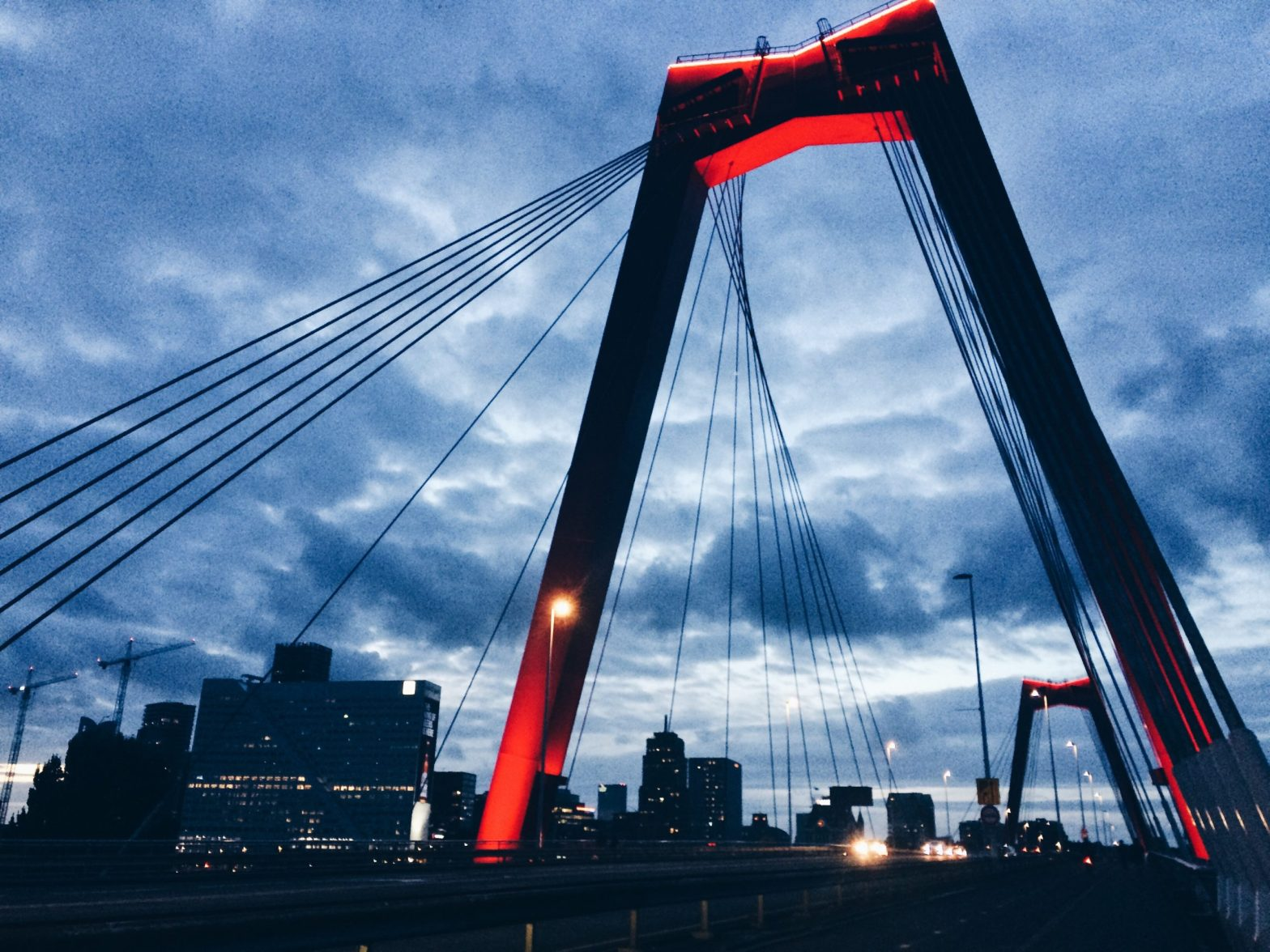A big red bridge against deep blue and moody sky in Rotterdam