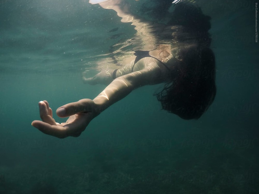 woman floating in the sea, seen from below the surface. The colours are dark and vague. Her hair and limbs move gently with the flow of the water.