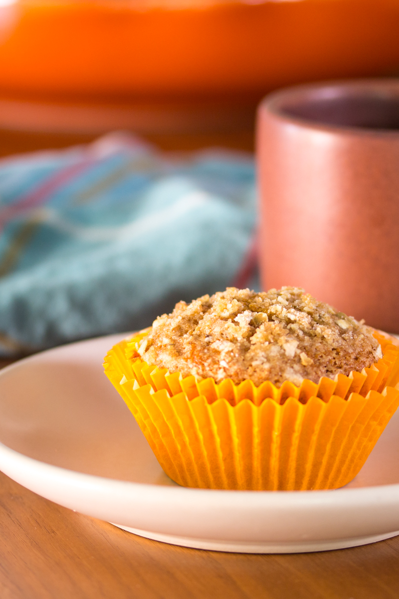 Pumpkin muffins made with fall spices, applesauce, and golden raisins, topped with pumpkin seed streusel.