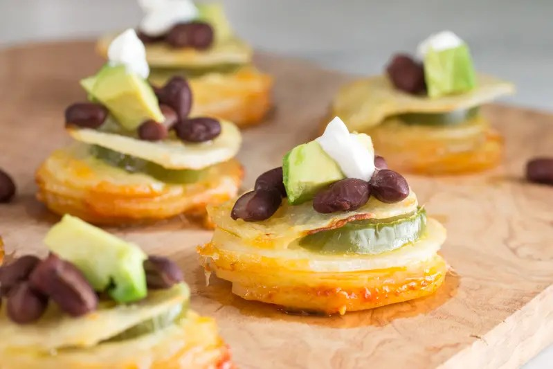 Bites of potato stacks, nacho style with cheese, black beans, salsa, avocado and a dollop of sour cream.