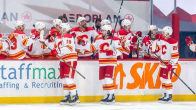 WINNIPEG, MB - JANUARY 14: Matthew Tkachuk #19, Rasmus Andersson #4 and Elias Lindholm #28 of the Calgary Flames celebrate a first period goal against the Winnipeg Jets with teammates at the bench at the Bell MTS Place on January 14, 2021 in Winnipeg, Manitoba, Canada. (Photo by Jonathan Kozub/NHLI via Getty Images)
