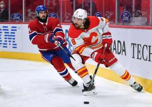 MONTREAL, QC - APRIL 14: Christopher Tanev #8 of the Calgary Flames looks to pass the puck against Phillip Danault #24 of the Montreal Canadiens in the NHL game at the Bell Centre on April 14, 2021 in Montreal, Quebec, Canada. (Photo by Francois Lacasse/NHLI via Getty Images)