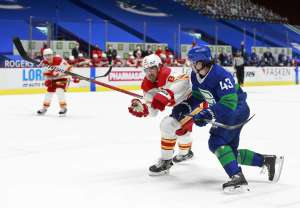 VANCOUVER, BC - MAY 16: Quinn Hughes #43 of the Vancouver Canucks checks Christopher Tanev #8 of the Calgary Flames during their NHL game at Rogers Arena on May 16, 2021 in Vancouver, British Columbia, Canada. Calgary won 6-5. (Photo by Jeff Vinnick/NHLI via Getty Images)