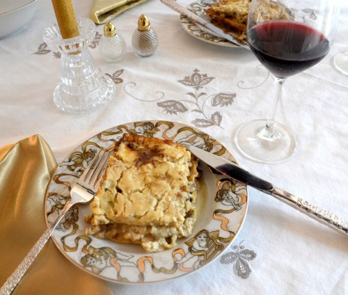 Square of Mushroom Marsala Lasagna on a Christmas plate with a glass of red off to the side.