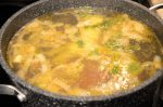dutch oven on stove top simmering with vegetables and water