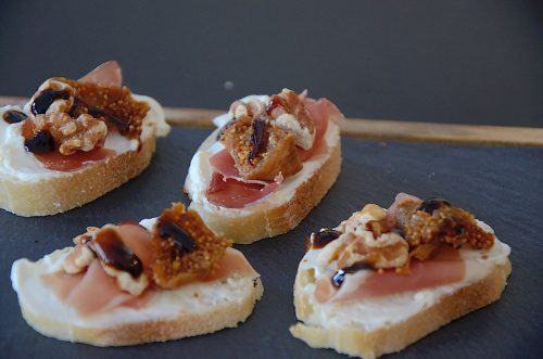 French baguette slices topped with cream cheese and a piece of prosciutto, dried fig and walnut