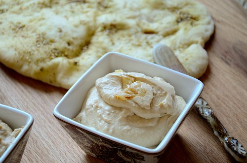 lemon garlic hummus in square bowl with flat bread in background