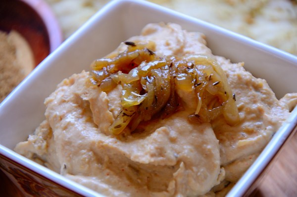 close up of hummus in a square pot with caramelized onion garnish