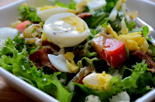 close up of frisee lettuce with bacon, tomato and hard boiled egg