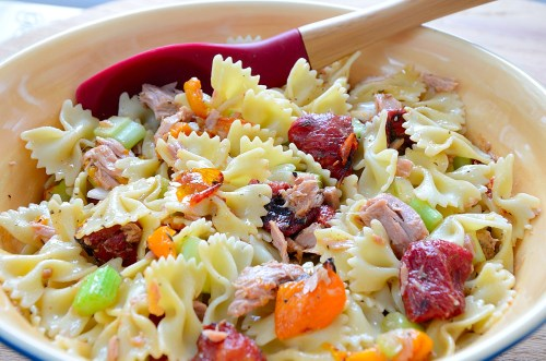 Bow Tie pasta in a bowl with roasted peppers and tomatoes.