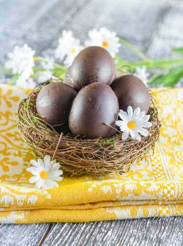 Vegan Chocolate Easter eggs in a vine nest surrounded by Daisies.