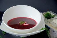 Polish Borscht soup in a bowl with sour cream and dill garnish