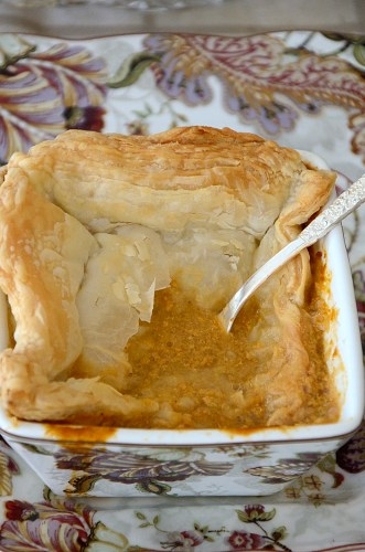 Spoon in square soup bowl, broken through puff pastry to lobster bisque